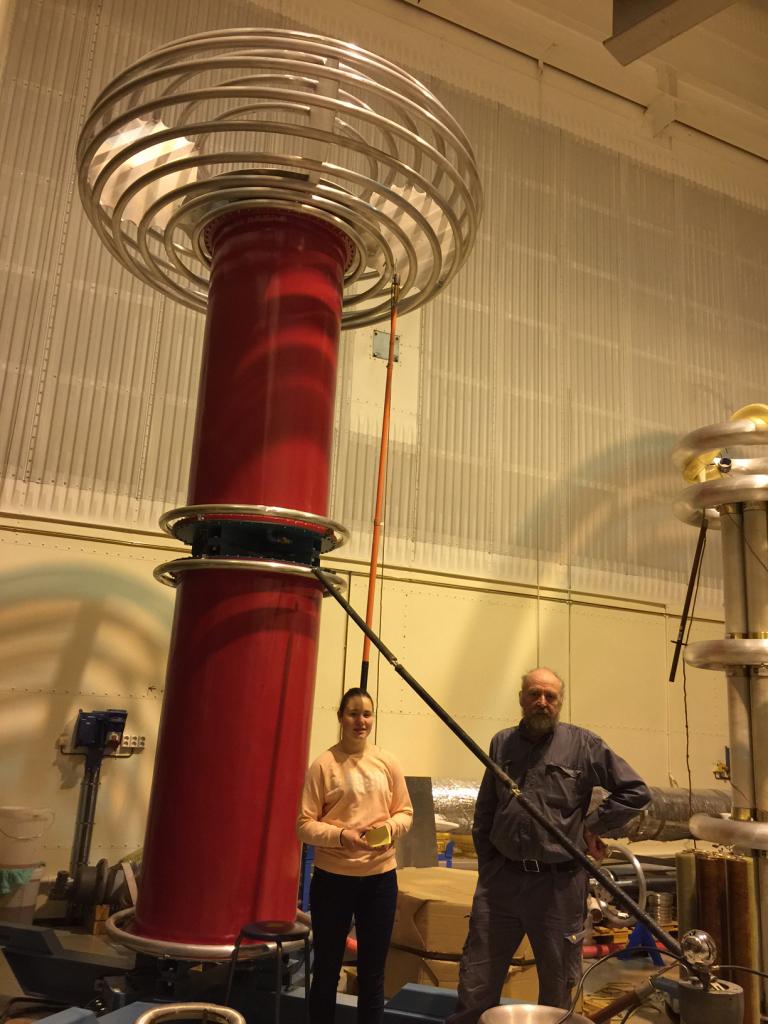 Horst og meg foran likespenningskilde. Den er på 800 000 volt. Et lite rundt batteri er på 1,5 volt. http://no.wikipedia.org/wiki/Likestr%C3%B8m