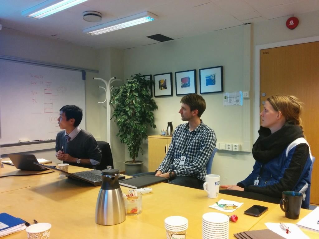 Assistant Professor Yuhiro Iwamoto holding a presentation on magnetic fluids, with SINTEF researchers Halvor Lund and Ingrid Snustad watching intently (Photo: Karl Yngve Lervåg)
