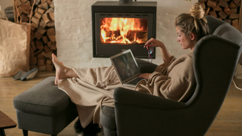 Woman working from home, with fireplace in the background