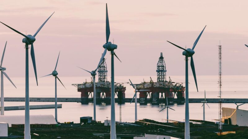 Wind turbines in the foreground, with oil platforms in the background.